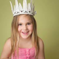 Happy, smiling girl wearing a white crown, princess pretend play